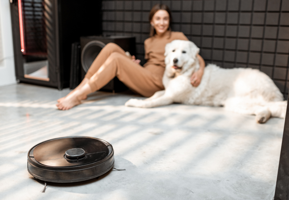 photo of a woman and a dog using a smart robot vacuum