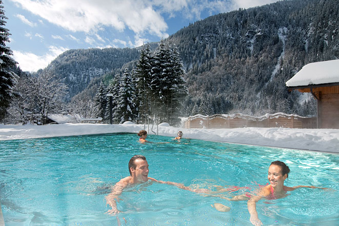 This is a heated above ground pool with people swimming in the cold weather