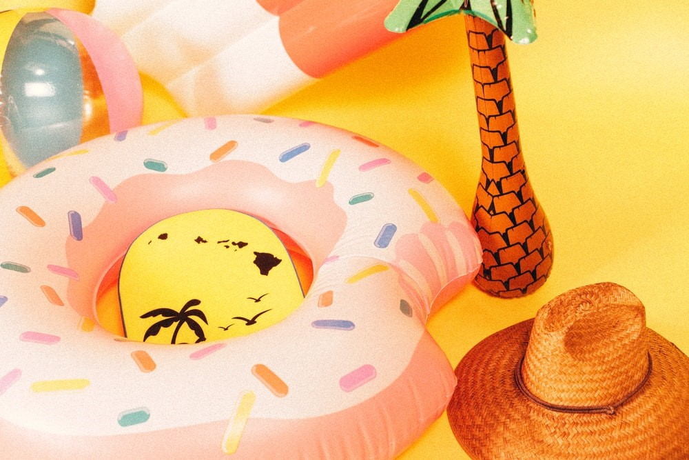 A donut-shaped floating ring, inflatable palm tree, and sun hat of Summer 2021: 6 Products That Will Solve Your Hot Weather Problems