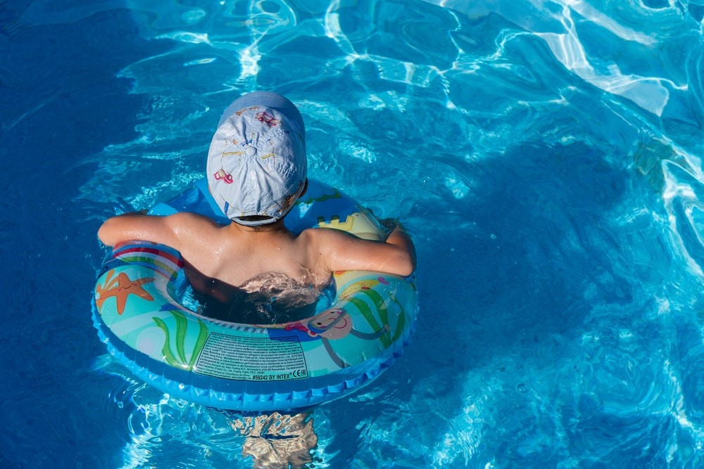 a boy swimming in the pool with a floating ring