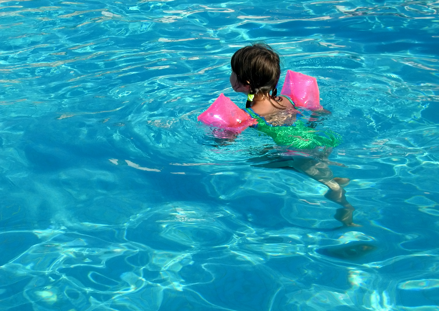 a toddler swimming in the pool alone wearing a floties