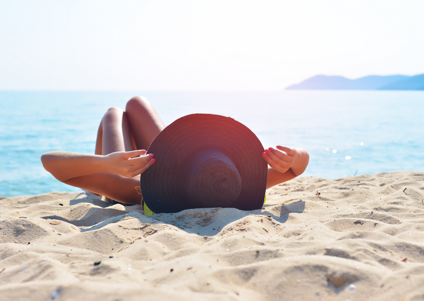 photo of woman lying in the sand under the sun