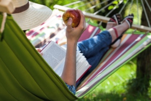 a woman lying in the hammock while eating an apple and reading a book