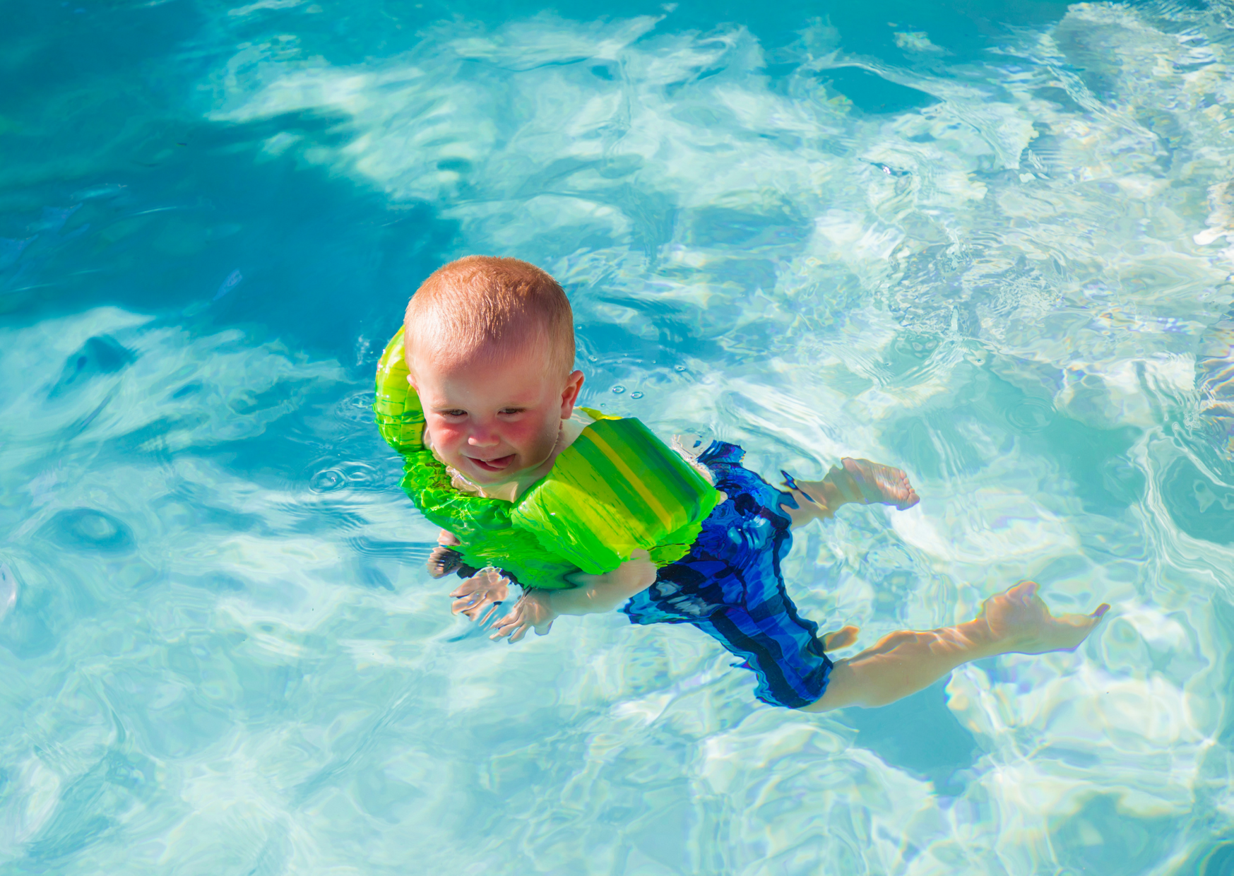 a toddler wearing a floaties while swimming in the pool