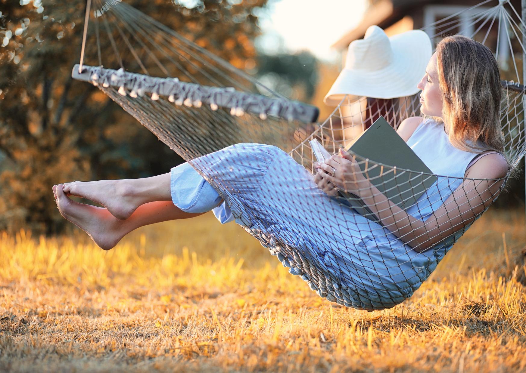 woman lying in a woven hammock