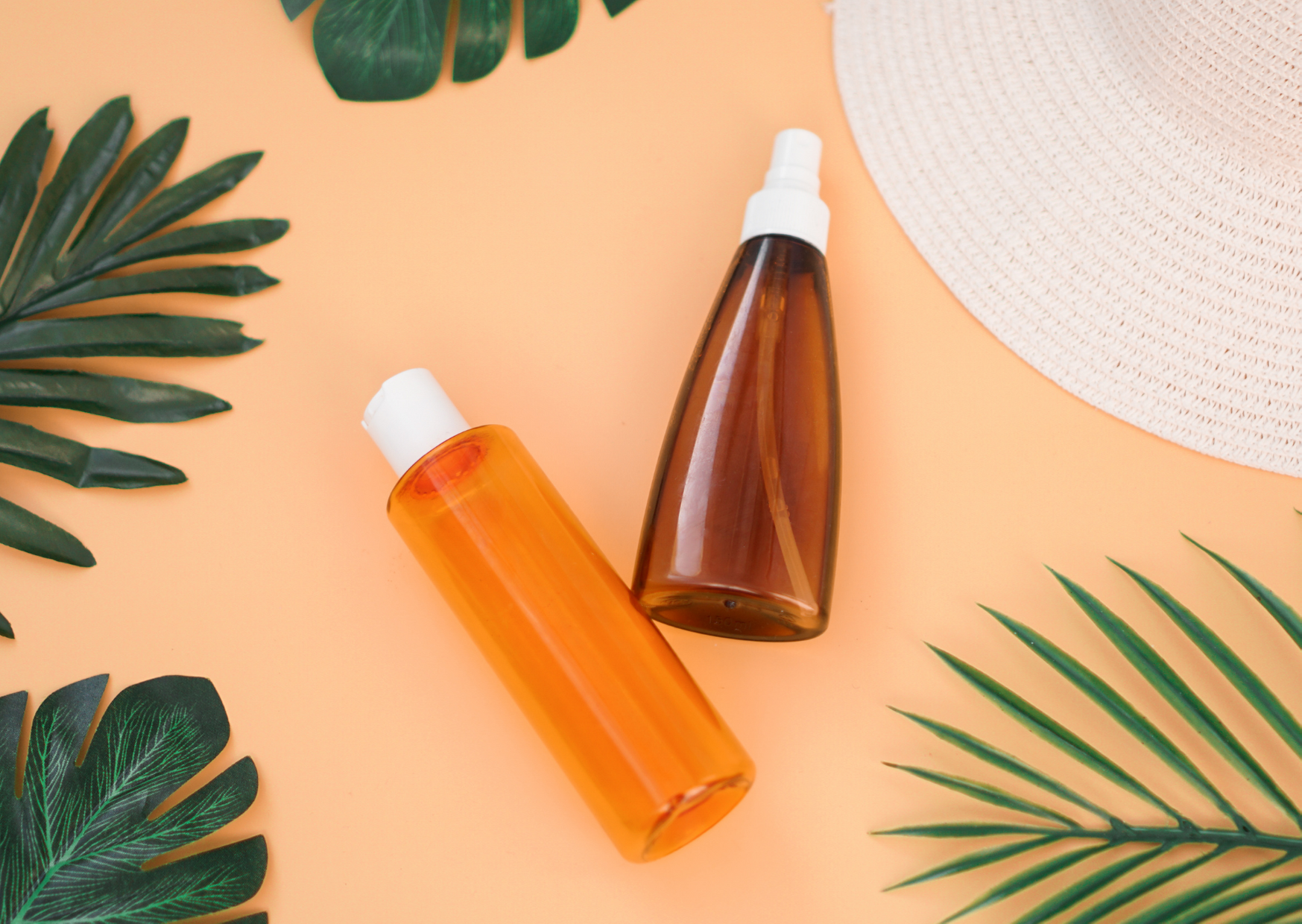 image of two spray bottles with coral background with palm leaves