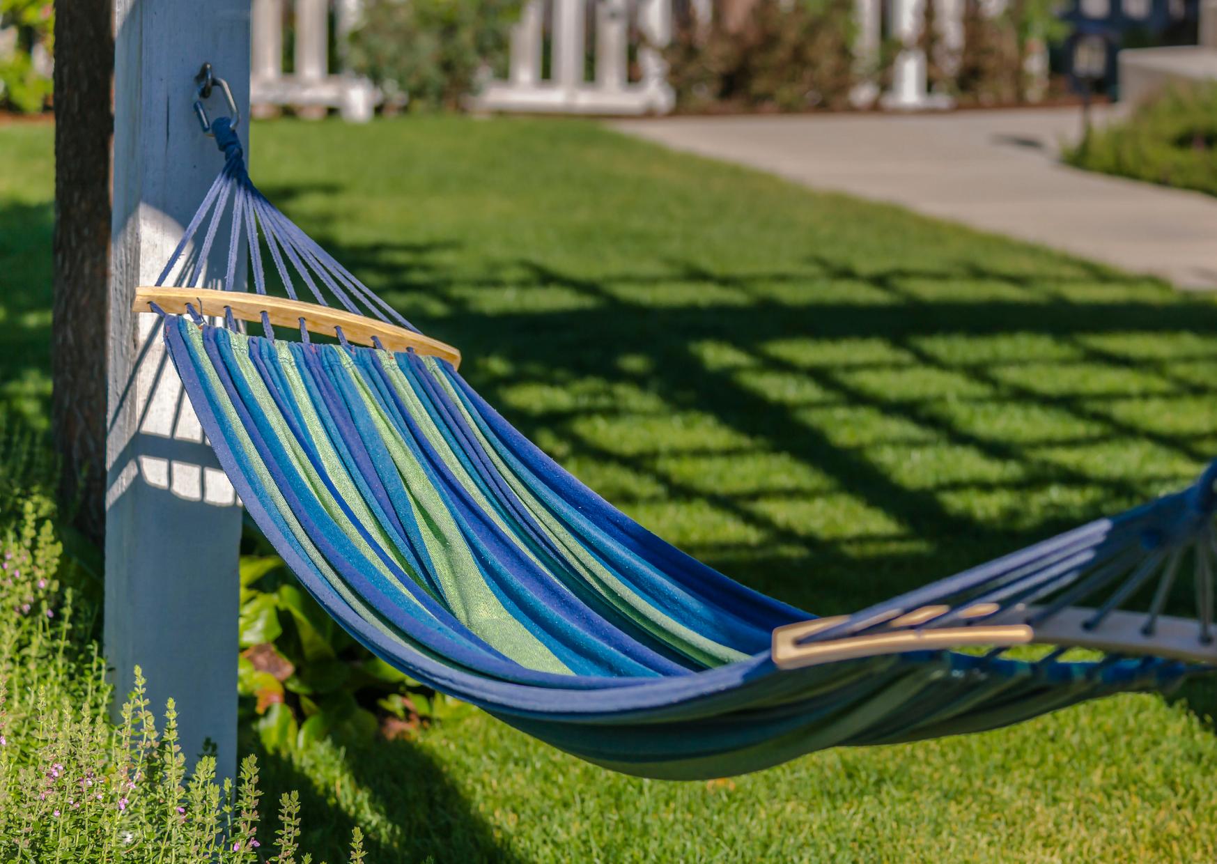 a blue and green stripe hammock in the backyard