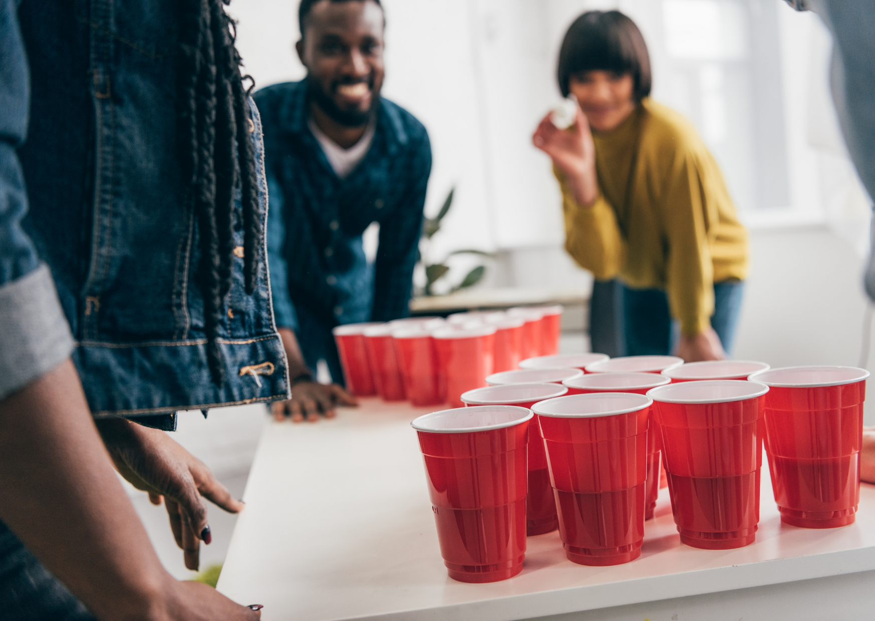 friends having a beer pong game of The Best Lawn Drinking Games for Adult Fun