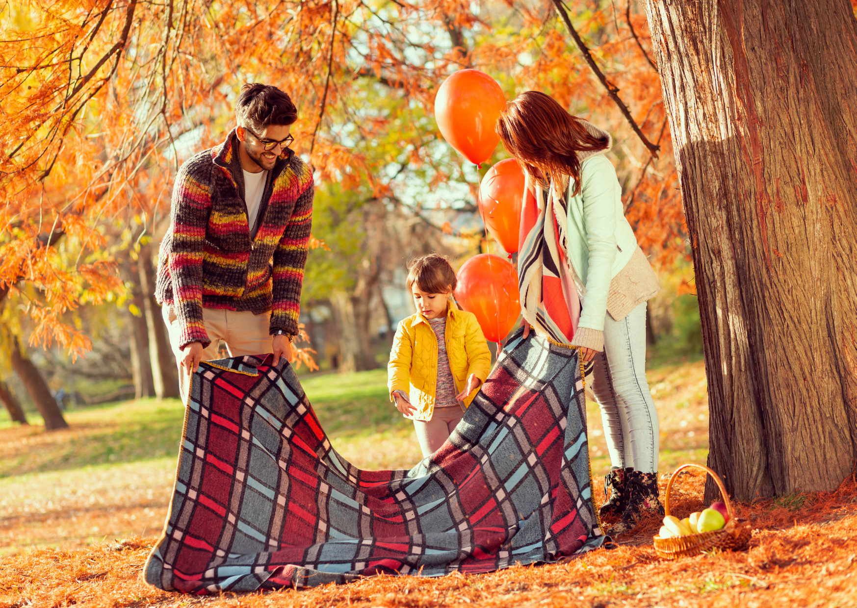 a family of three having a picnic under the tree