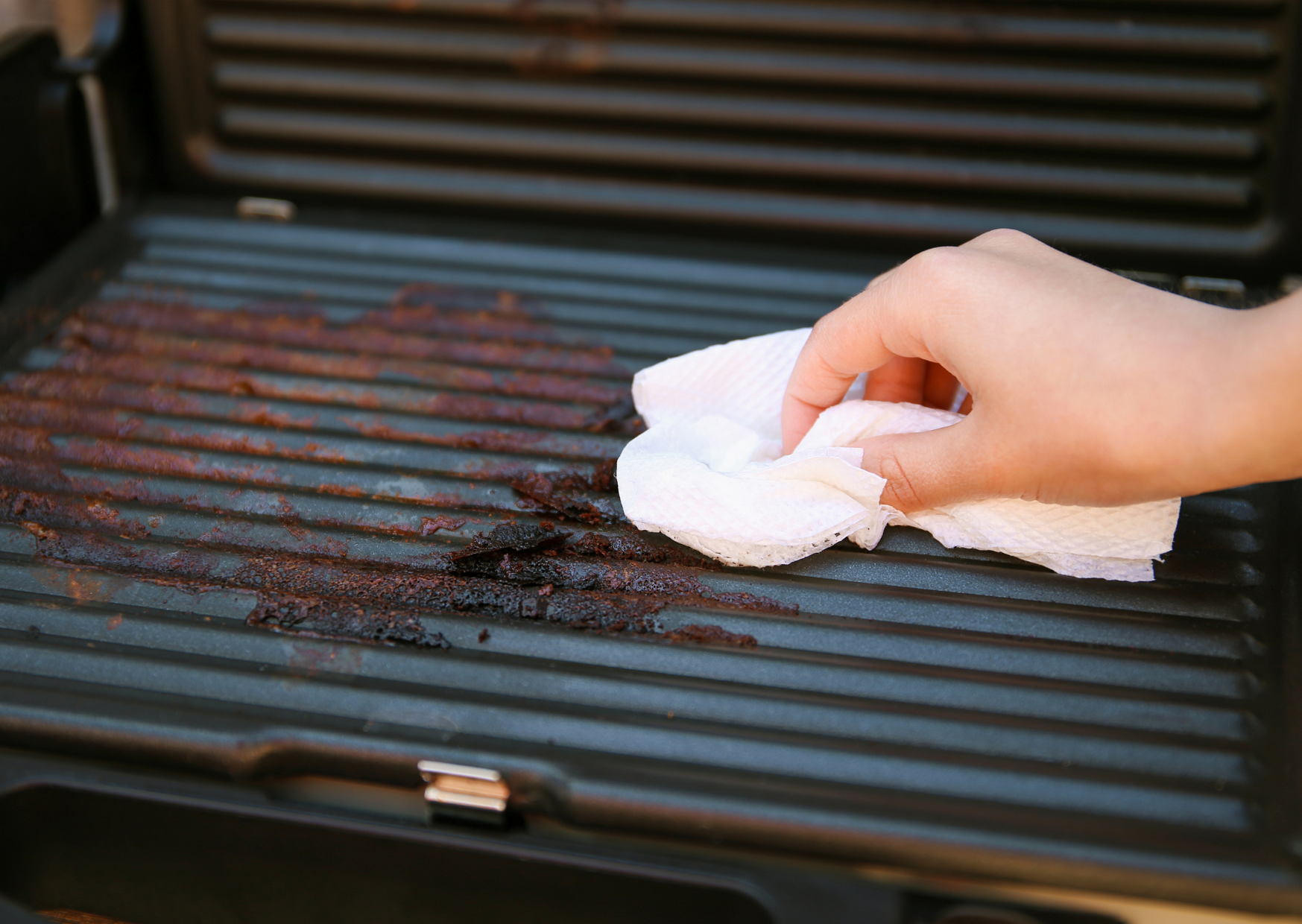 cleaning the electric grill with white cloth
