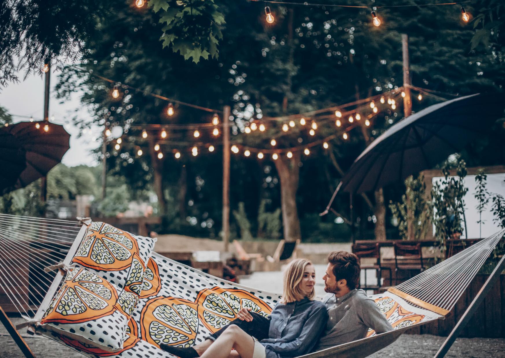 a couple sitting in hammock in the garden