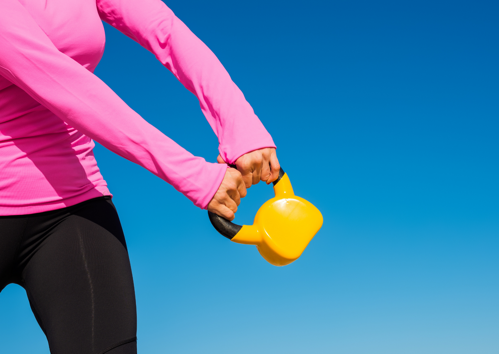 a woman wearing pink holding a yellow kettle bell