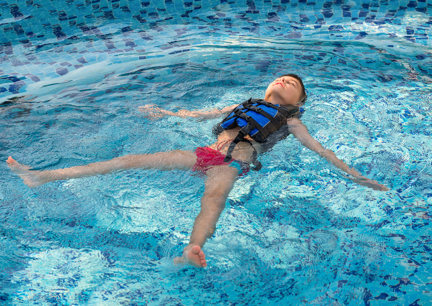 toddler floating in he pool wearing a vest