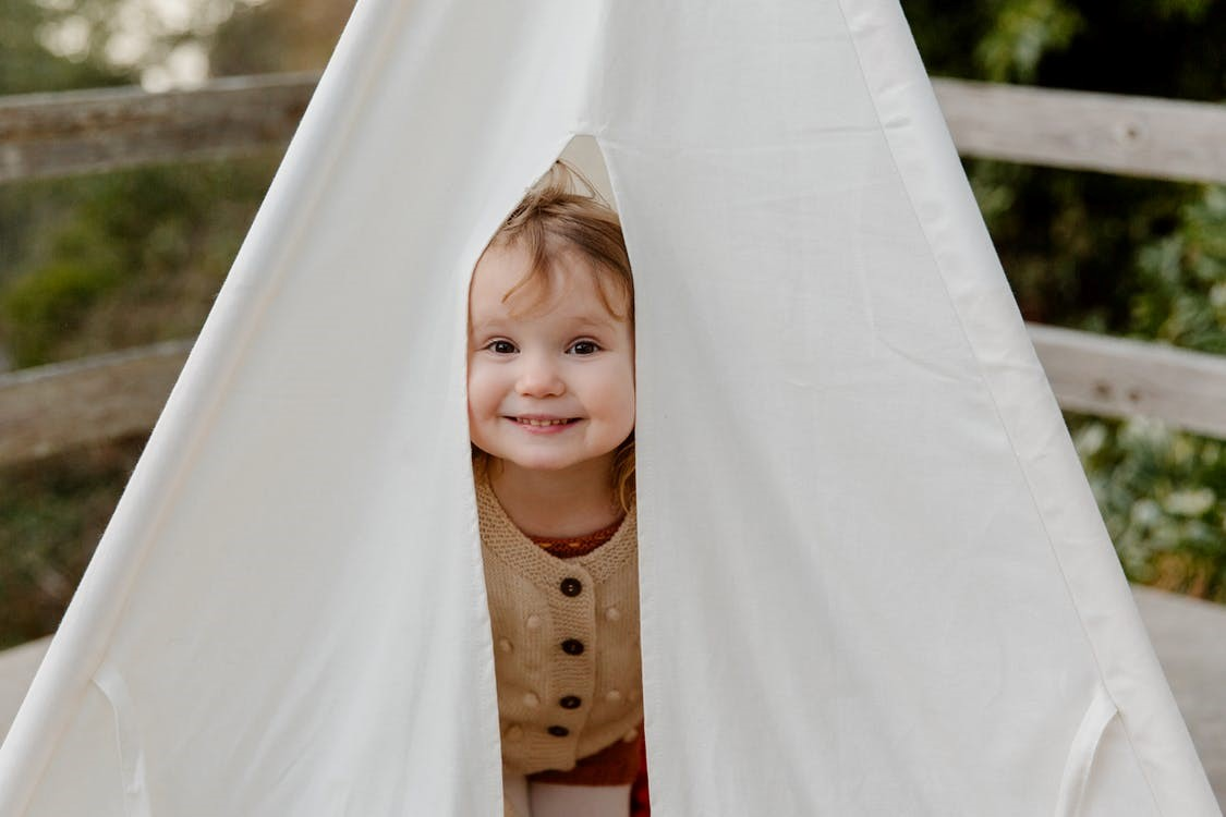 A toddler peeking out of a white tent