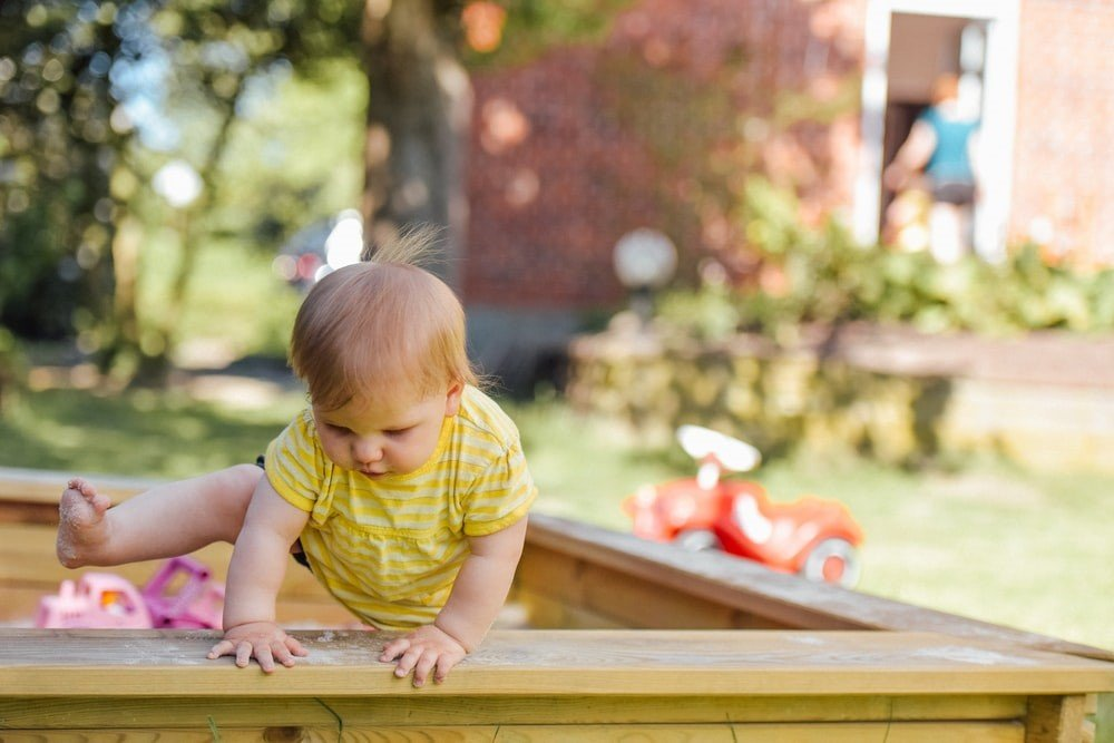 A toddler getting out of the sandbox
