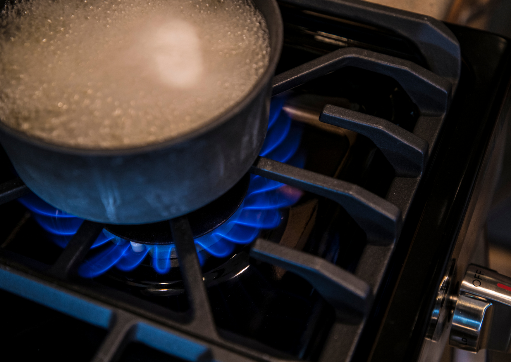a boiling water in a pot under the stove