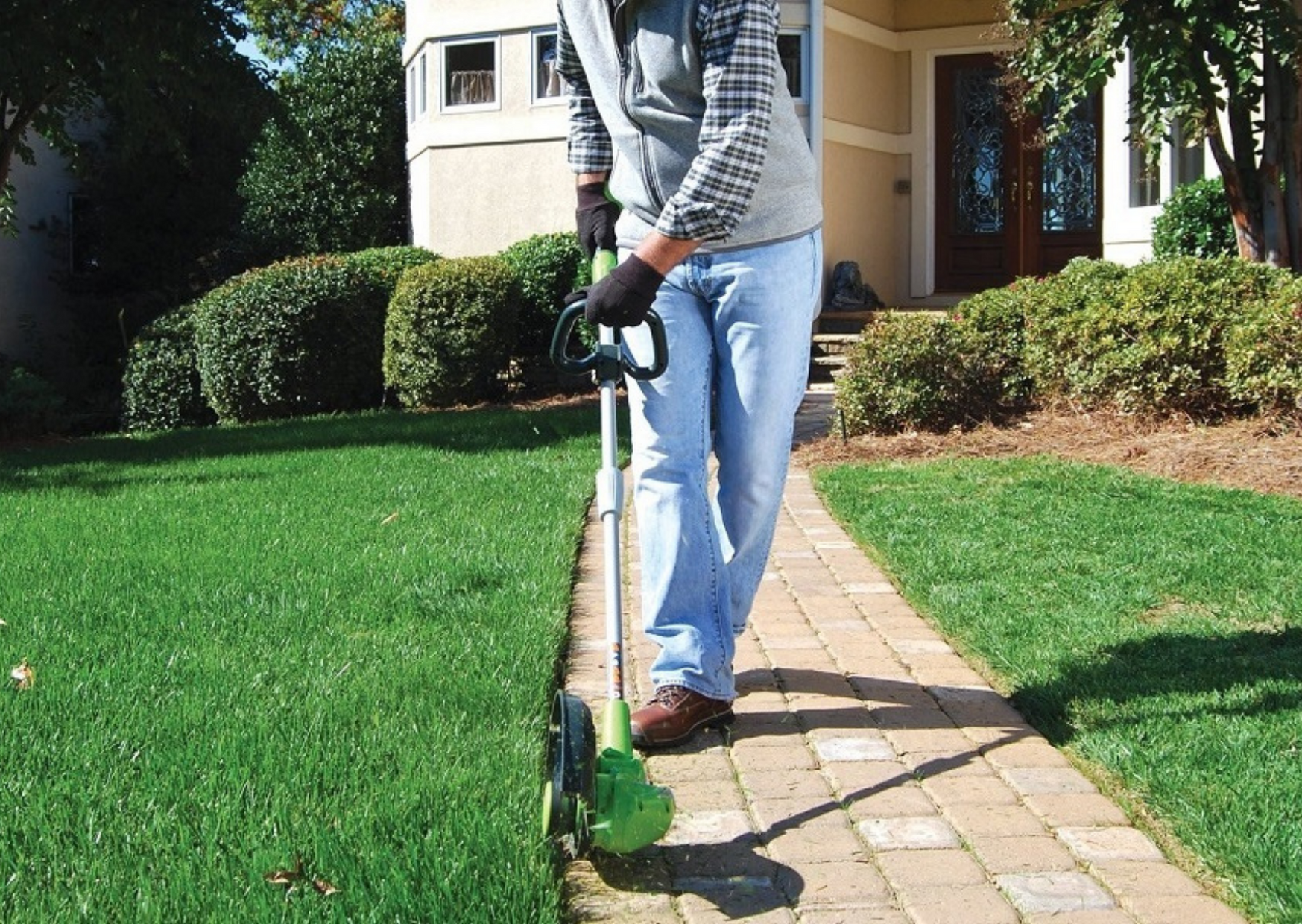 image of a man using a manual lawn edger in his garden