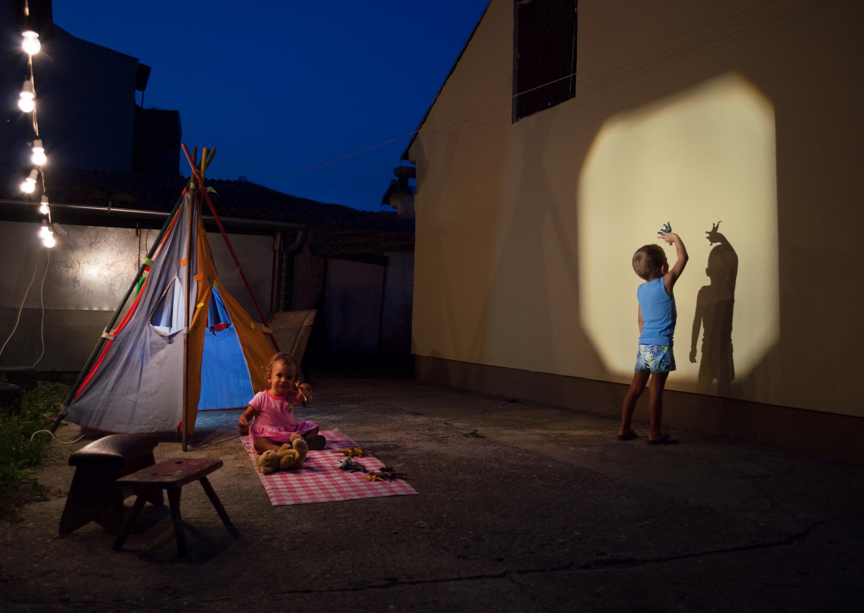 Kids playing shadow in backyard in Fun Things To Do Camping In Your Backyard