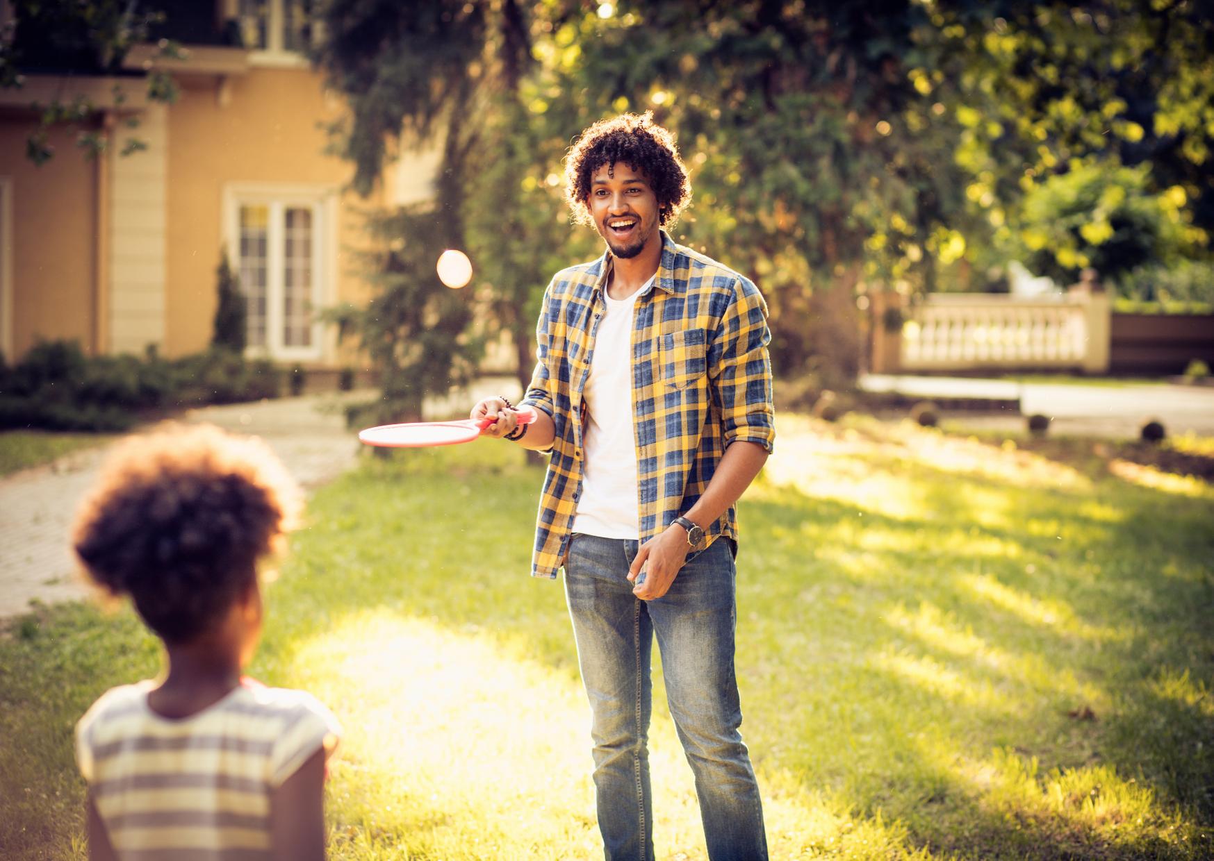 Man having fun with kids in backyard in Fun Things to Do In your Backyard When You Are Bored