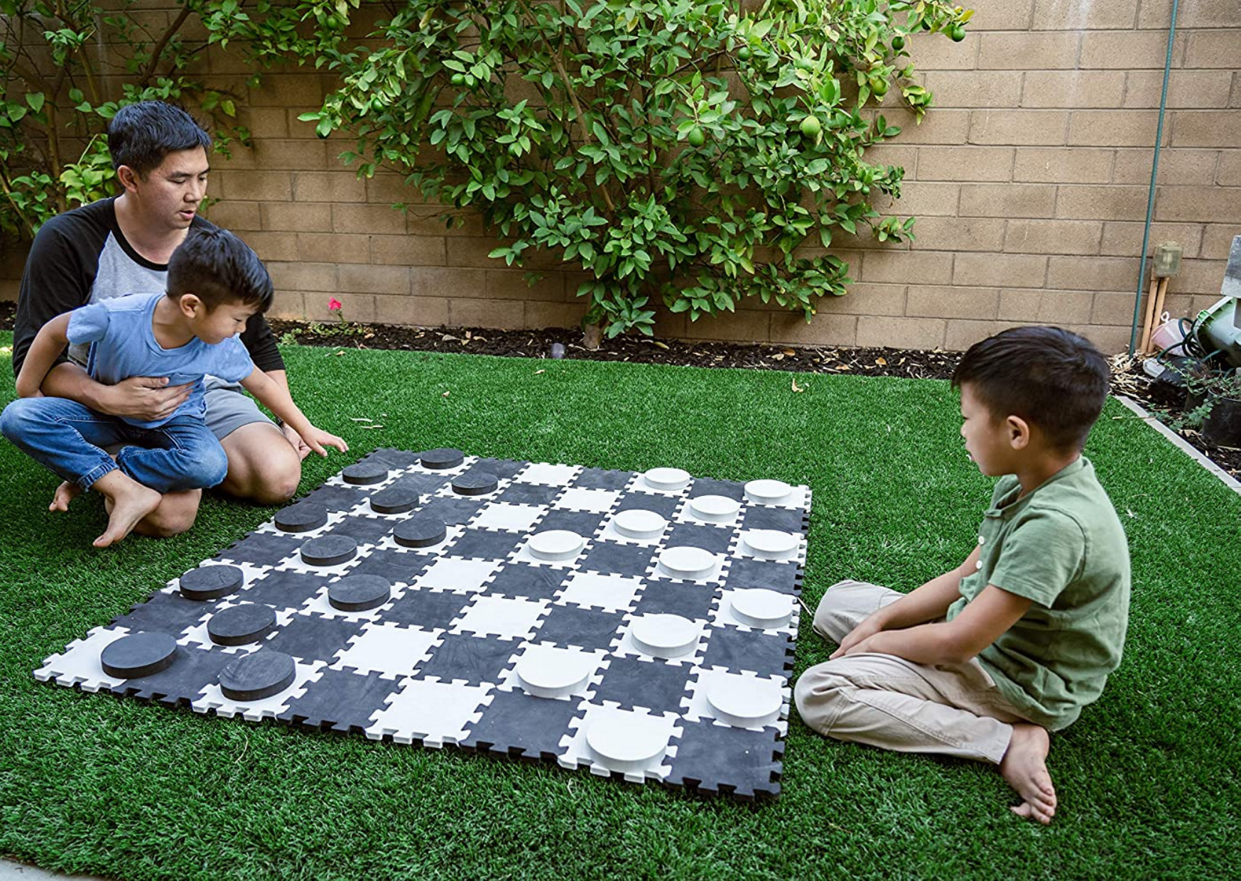 family playing board game outdoor of The Three Best Giant Connect Four Lawn Games to Encourage Backyard Fun