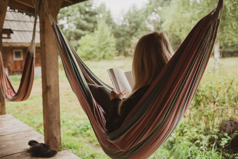 A young girl reading a book in a hammock