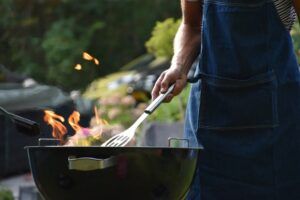 A close-up image of a person grilling steaks