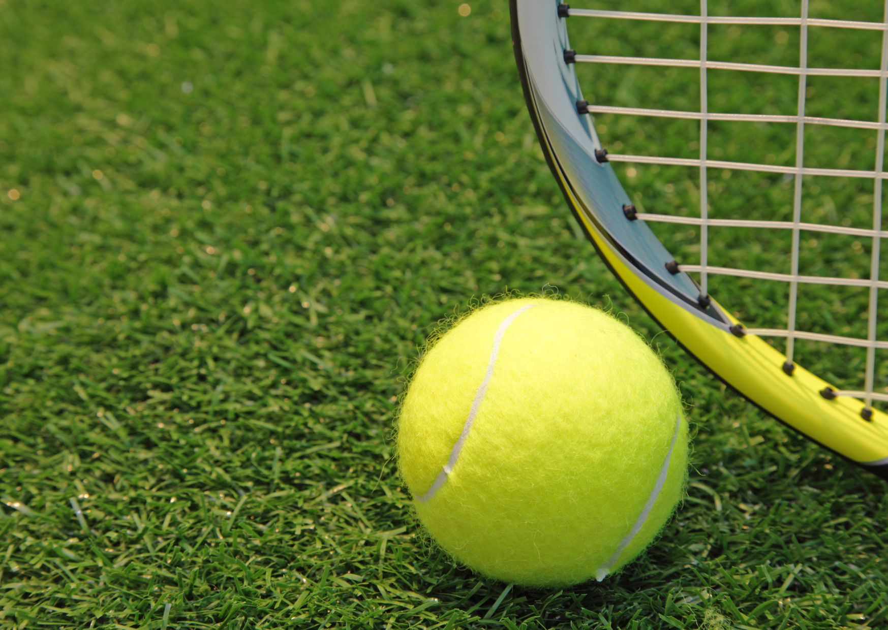 a yellow tennis ball in the grass of Is Lawn Tennis an Indoor Game?