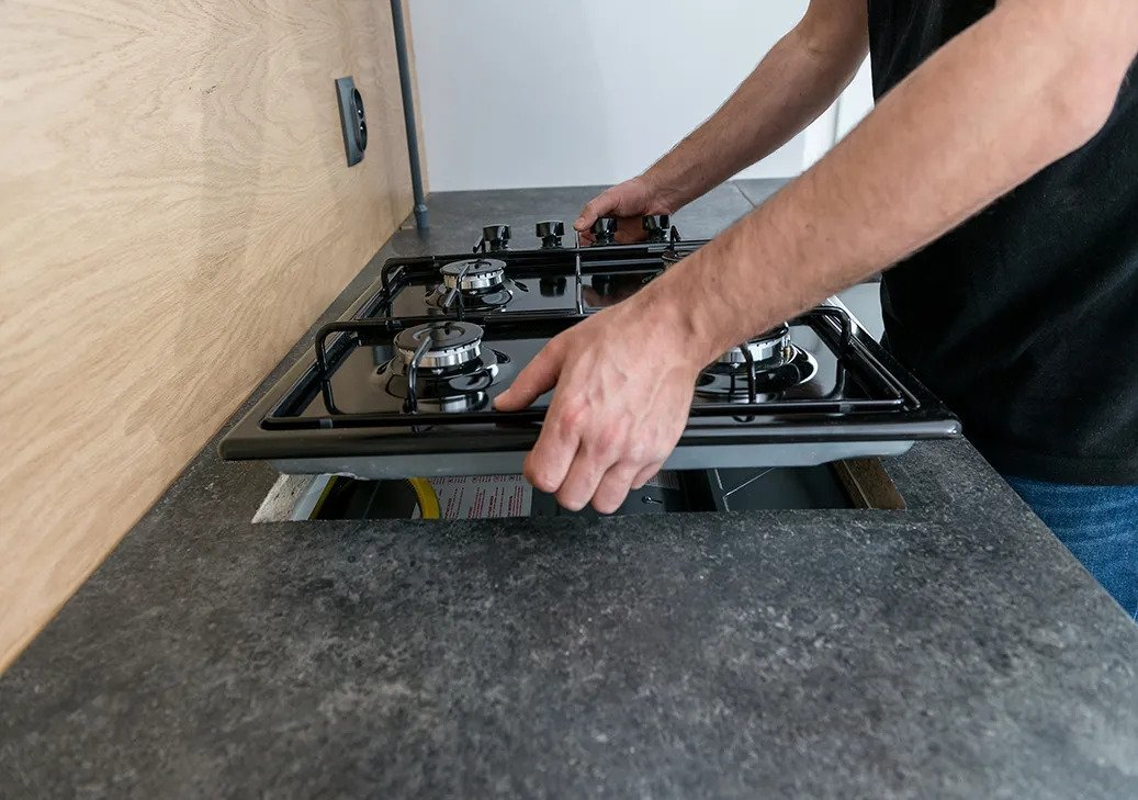 Man installing a gas hob in a kitchen