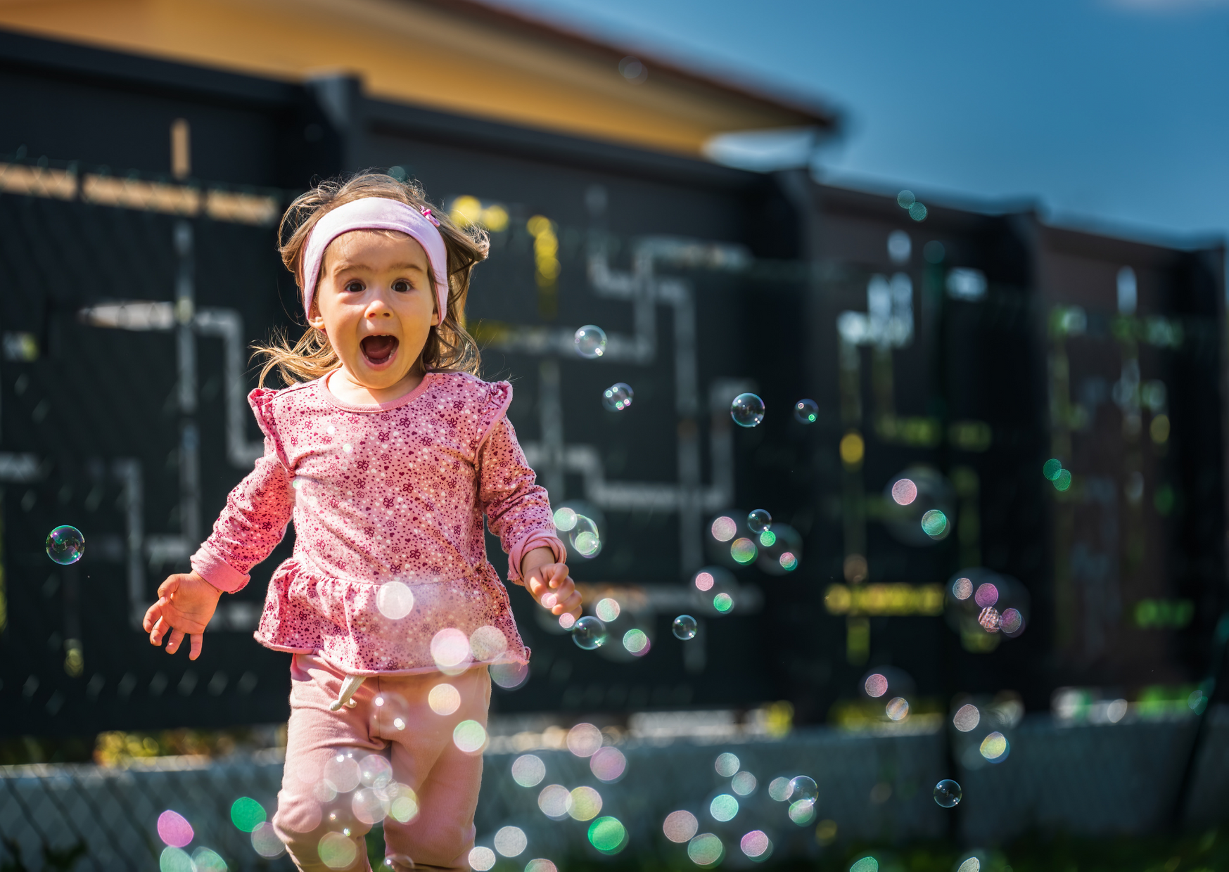 2 years old playing bubbles in backyard