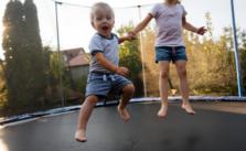 Kids having fun in the trampoline in backyard