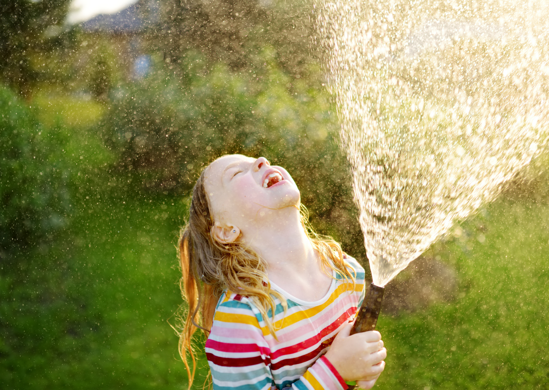 Kid playing a hose of The Best Six Water Activities to Stay Cool in the Summer