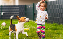 Kids playing in backyard with her dog
