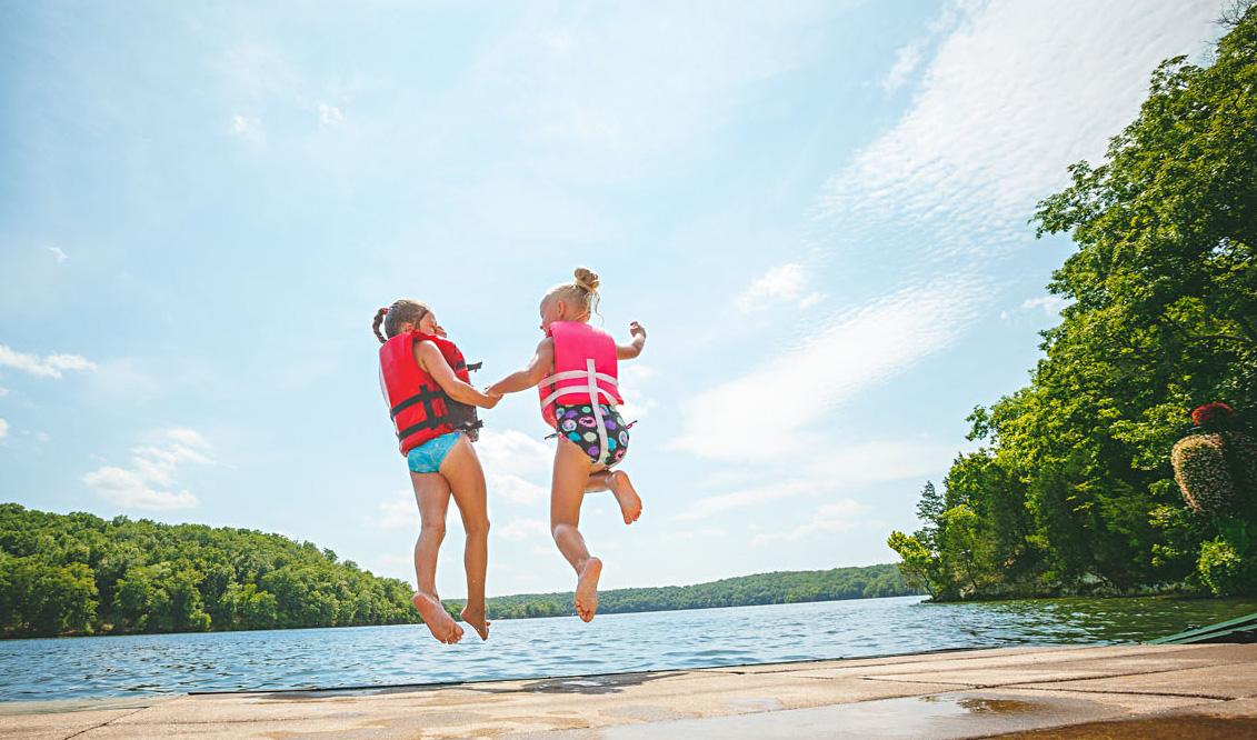 2 kids jump in the beach